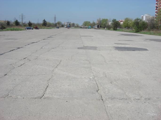 Fragment wschodniej, nie używanej części drogi startowej w kierunku zachodnim i ulicy Stella-Sawickiego. Dobrze widoczna linii wysokiego napięcia z czerwonymi balonikami ostrzegawczymi dla pilotów. 2009r.
