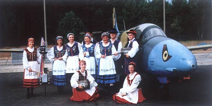 Uroczystość wręczenia sztandaru 3 Dywizjonowi Lotniczemu. Zespół wokalno-muzyczny w strojach kaszubskich obok podstawowego samolotu w Dywizjonie. 1997r.