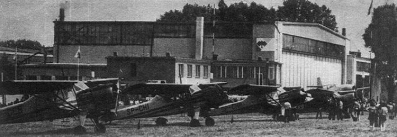 Lotnisko Gliwice 1980 rok. Na pierwszym planie samoloty PZL-101. Przed hangarem, na postumencie myśliwiec Jak-23. Zdjęcie B. Koszewski