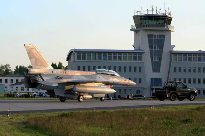 F-16 D nb 4087 na tle portu lotniczego. Samolot właśnie przybył do Rzeczypospolitej. Ma jeszcze zasłonięte Polskie znaki rozpoznawcze, a widoczne amerykańskie. Samolot jest holowany standardowym ciągnikiem. 2008r.