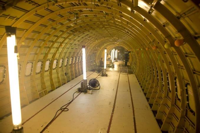 Wnętrze kabiny pasażerskiej Boeing 737 z zamontowaną podłogą. Do bordowych profili w podłodze przytwierdzone zostaną szyny, a do nich fotele. Widać doskonale konstrukcje kadłuba. Przenośne lampy zapewniają oświetlenie. Renton 2011r.