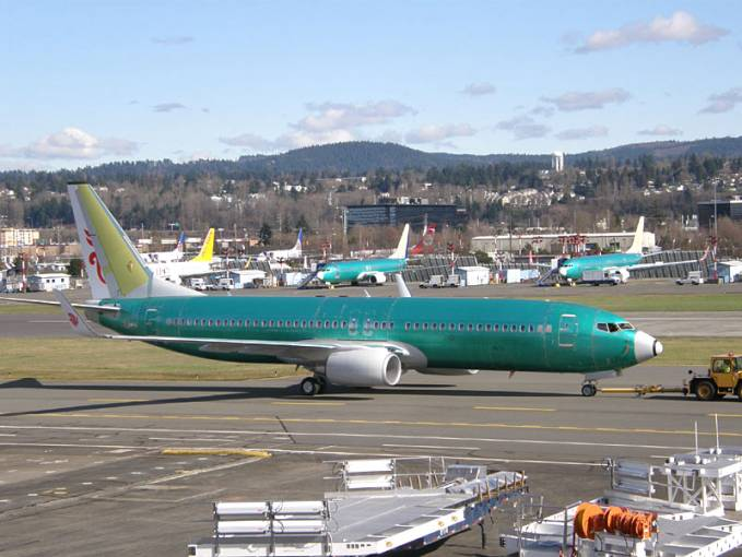 Ciągnik dyszlowy przeciąga samolot Boeing 737 na stojankę. Renton 2011r.